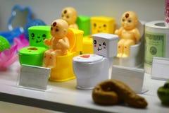 Смешные шары туалета, крены туалетной бумаги и сувениры кормы на дисплее на полке стоковые изображения