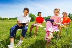 Смешные эскиз-доски владением детей и сидят снаружи Стоковые Фото