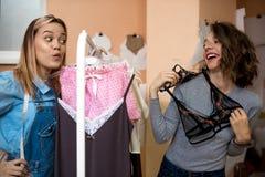 2 смешных девушки пробуют дальше бюстгальтеры в выставочном зале Стоковые Изображения