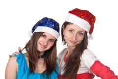 2 смешных девушки в крышках Санта Клауса Стоковые Фотографии RF