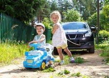 2 смешных дет пробуя отбуксировать реальный автомобиль веревочкой Стоковая Фотография RF