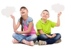 2 смешных дет сидя на поле с бумажными облаками в руках Стоковые Изображения