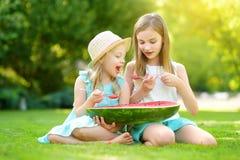 2 смешных маленьких сестры есть арбуз с ложками outdoors на теплый и солнечный летний день Здоровые натуральные продукты для дете стоковая фотография