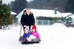 2 смешных маленьких сестры имея езду на лопаткоулавливателе снега на зябкий зимний день Дети играя в снеге во время зимы ломают Стоковое Изображение RF
