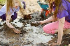 2 смешных маленькой девочки играя в большой влажной лужице грязи на солнечный летний день Дети получая пакостный пока выкапывающ  стоковая фотография rf