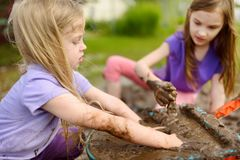 2 смешных маленькой девочки играя в большой влажной лужице грязи на солнечный летний день Дети получая пакостный пока выкапывающ  стоковые фото