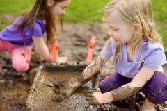 2 смешных маленькой девочки играя в большой влажной лужице грязи на солнечный летний день Дети получая пакостный пока выкапывающ  стоковое изображение rf
