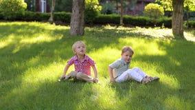 2 смешных мальчика играют на зеленой траве в парке каникула территории лета katya krasnodar видеоматериал