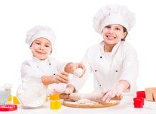 2 смешных маленьких кашевара подготавливая тесто Стоковое Фото