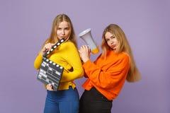 2 смешных молодых белокурых девушки сестер близнецов держа классическое черное clapperboard создания фильма, клекот на мегафоне стоковые изображения
