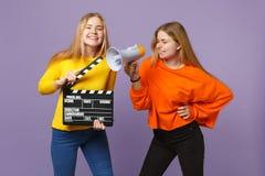 2 смешных молодых белокурых девушки сестер близнецов держа классическое черное clapperboard создания фильма, клекот на изолирован стоковое фото