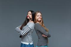 2 смешных молодой женщины делая усик с их волосами стоковые изображения