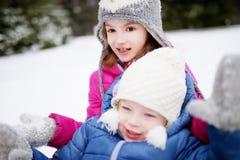2 смешных прелестных маленьких сестры имея потеху совместно в парке зимы Стоковые Изображения RF