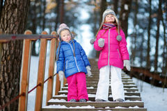 2 смешных прелестных маленьких сестры имея потеху совместно в парке зимы Стоковые Фото