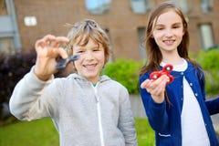 2 смешных друз играя с обтекателями втулки непоседы на спортивной площадке Популярная стресс-сбрасывая игрушка для детей и взросл Стоковое Изображение RF