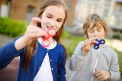 2 смешных друз играя с обтекателями втулки непоседы на спортивной площадке Популярная стресс-сбрасывая игрушка для детей и взросл Стоковое Изображение