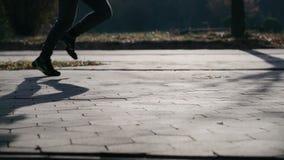 Смещение бежит в рамке слева направо, отражающ тень на следе Только ноги спортсмена видимы акции видеоматериалы