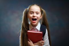 Смеясь длинный окрик Красной книги владением школьницы волос стоковое изображение