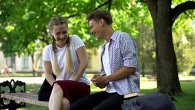 Смеясь друзья сидя на стенде в парке, говоря весьма смешную историю, шутка стоковые фото
