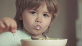 Смеясь милый ребенок ребенка сидя в высоком стульчике и есть на предпосылке кухни r Милая еда ребенка видеоматериал