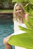 Смеясь модель сидя в саде роскошного отеля стоковые изображения