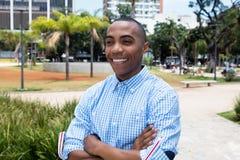 Смеясь над Афро-американский человек с пересеченными оружиями стоковые фотографии rf