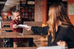 Смеясь над бизнесмен с бумагами говоря к ее коллеге во время встречи в кафе Стоковые Фотографии RF