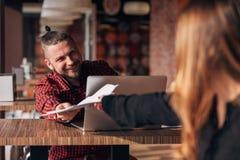 Смеясь над бизнесмен с бумагами говоря к ее коллеге во время встречи в кафе Стоковое Изображение