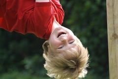 Смеясь над висеть мальчика вверх ногами в спортивной площадке Стоковое Фото