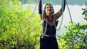 Смеясь над женщина ведьмы в черных одеждах на береге озера имеет потеху и танцует с цепями в ее руках Hallowee акции видеоматериалы