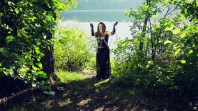 Смеясь над женщина ведьмы в черных одеждах на береге озера имеет потеху и танцует с цепями в ее руках сток-видео