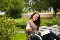 Смеясь над женщина при книга представляя большие пальцы руки вверх Стоковое фото RF