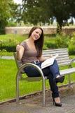 Смеясь над женщина при книга представляя большие пальцы руки вверх Стоковая Фотография
