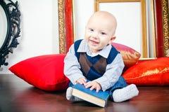 Смеясь над маленький младенец с книгой Стоковая Фотография