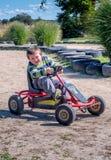 Смеясь над мальчик на красном автомобиле педали стоковое фото
