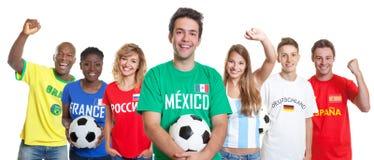 Смеясь над мексиканский сторонник футбола с шариком и вентиляторы от другого стоковые фотографии rf