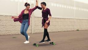 Смеясь над молодая девушка битника будучи ученным skateboarding другом который поддерживает ее удерживание ее рука Slowmotion акции видеоматериалы