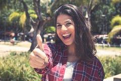 Смеясь над молодая кавказская женщина показывая большой палец руки вверх стоковые изображения