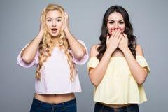 2 смеясь над 2 подругами Уши одной девушки близкие, один рот девушки близкий на белой предпосылке Стоковые Изображения RF