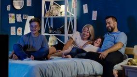 Смеясь над семья наслаждаясь ТВ на ноче Стоковое Изображение