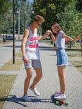 Смеясь над собрат уча красивому катанию девушки на longboard в парке на естественной запачканной предпосылке Стоковые Изображения RF