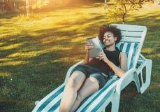 Смеясь над черная женщина на кушетке с цифровой пусковой площадкой стоковое фото