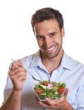 Смеясь над латинский человек есть салат стоковая фотография rf