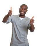 Смеясь над африканский человек показывая оба большого пальца руки Стоковое Фото