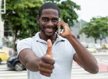 Смеясь над африканский человек с бородой на телефоне показывая большой палец руки вверх стоковые фото