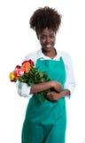 Смеясь над Афро-американский женский флорист с вьющиеся волосы и зеленой рисбермой Стоковая Фотография RF