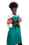 Смеясь над Афро-американский женский флорист с вьющиеся волосы и зеленой рисбермой Стоковые Фото