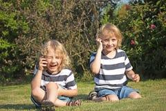 2 смеясь над белокурых мальчика вызывают outdoors Стоковая Фотография