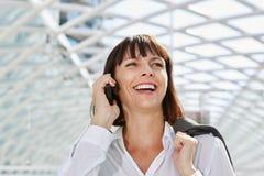 Смеясь над бизнес-леди говоря на мобильном телефоне в станции Стоковые Фотографии RF