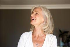 Смеясь над более старая женщина стоя внутренний дом Стоковое Фото